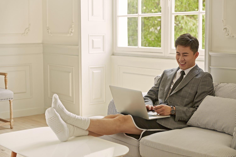 Un homme télétravaille depuis son domicile, sur son canapé, avec son ordinateur portable